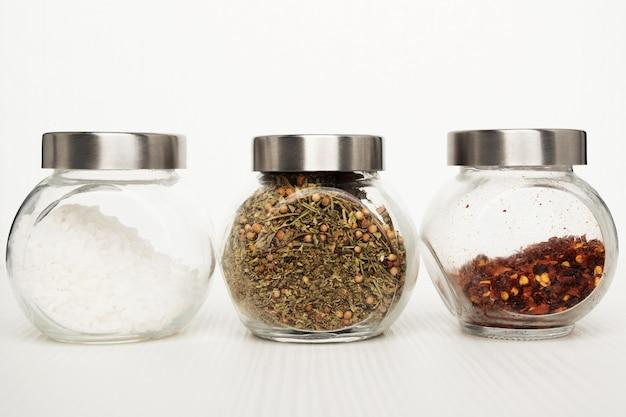Instellen voor het koken van heerlijke gerechten. zeezout, kruidenmix, hete chilipeper op een witte achtergrond