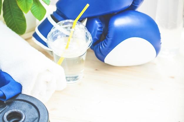 Instellen voor sport, handdoek, bokshandschoenen, halter en een fles water op een lampje
