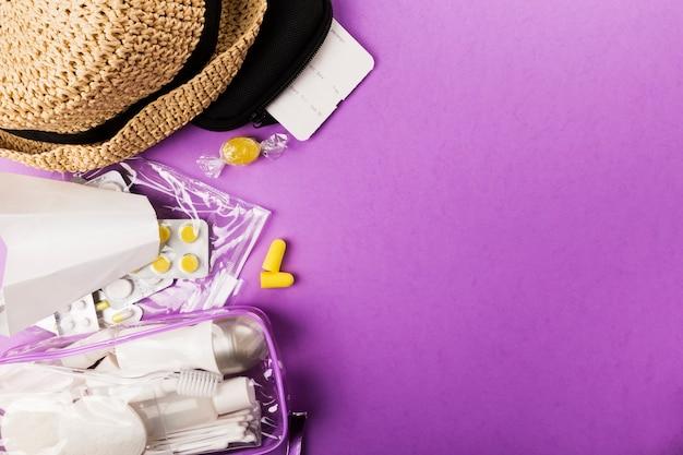 Instellen voor vlucht kleine flesjes met cosmetica, hoed, papieren vliegtuig, oordopjes, medicijnen, vliegticket en documenten op paars. bovenaanzicht, kopie ruimte
