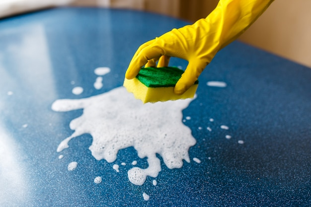 Instellen voor voorjaarsschoonmaak. vrouw hand in gele handschoen schoon, brood paneermeel op huis of op kantoor af te vegen.