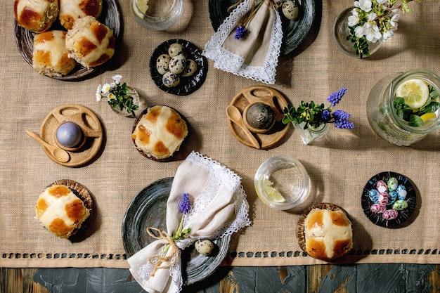 Instelling van de tabel voor pasen met gekleurde en chocolade-eieren, warme kruisbroodjes, boeket bloemen, lege keramische plaat met servet, glas limonade drankje op houten tafel met textiel tafelkleed
