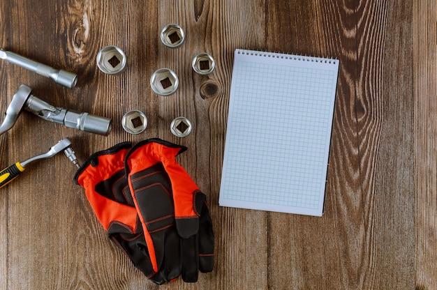 Instelling van hulpmiddelen voor automonteur, werkhandschoenen in moersleutel moersleutel auto spiraal blocnote houten achtergrond