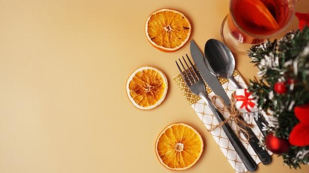 Instelling voor feestelijk kerstdiner op gouden tafel met nieuwjaarsdecoratie en droge sinaasappels