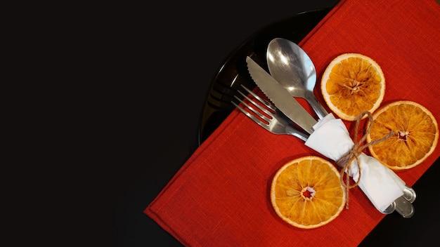 Instelling voor feestelijk kerstdiner op zwarte tafel met nieuwe jaar droge sinaasappels
