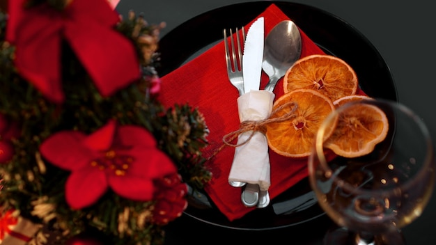 Instelling voor feestelijk kerstdiner op zwarte tafel met nieuwjaarsdecoratie en droge sinaasappels