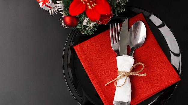 Instelling voor feestelijk kerstdiner op zwarte tafel met nieuwjaarsdecoratie