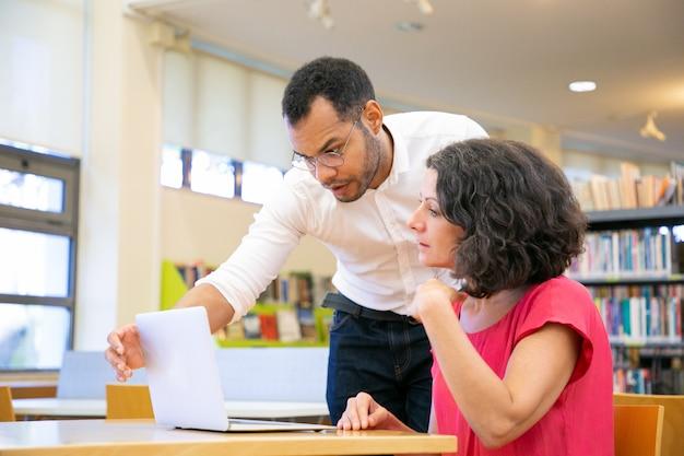 Instructeur die het studentenwerk in bibliotheek controleert