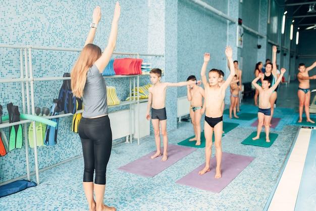 Instructeur en groep kinderen die oefeningen doen