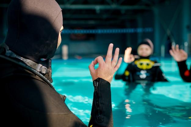 Instructeur en twee duikers, cursus in duikschool