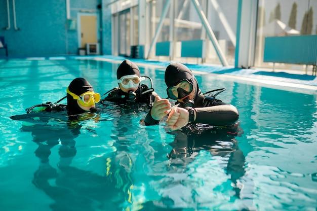 Instructeur en twee duikers in aqualungs, duikles in duikschool. mensen leren onder water te zwemmen met duikuitrusting, interieur van het binnenzwembad op de achtergrond, groepstraining