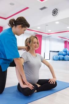 Instructeur helpt bij zwangere kolomoefeningen