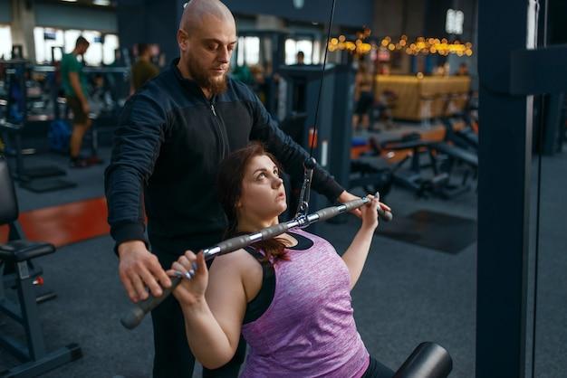 Instructeur helpt vrouw met overgewicht op fitnessapparaat, sportschool
