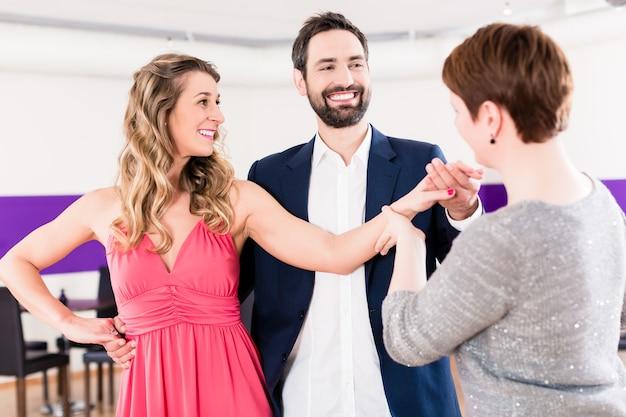 Instructeur in dansschool met een paar man en vrouw