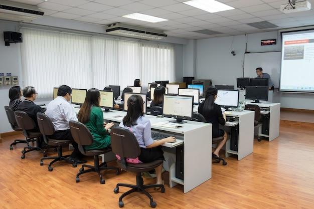 Instructeur lesgeven software studenten gebruiken op computerlokaal.