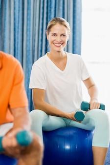 Instructeur met behulp van oefening bal en gewichten