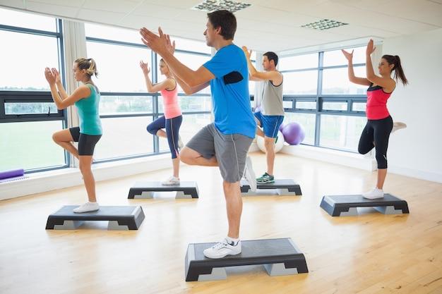 Instructeur met fitnessklasse die de oefening van de stapaerobics uitvoert