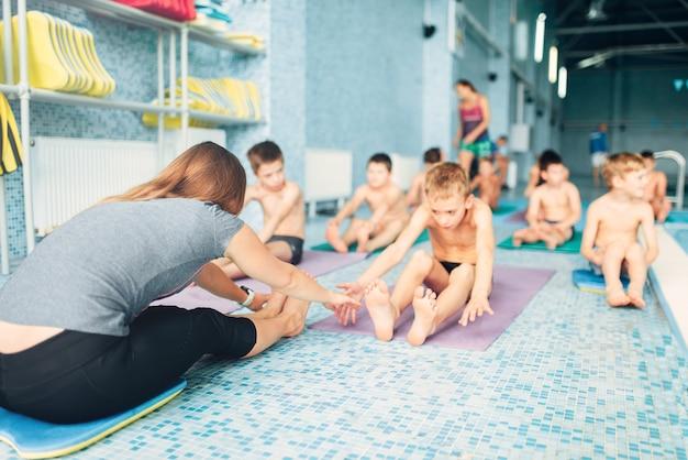 Instructeur met kinderen die oefeningen doen