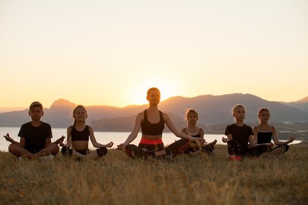 Instructeur traint yoga-kinderen in de bergen aan de oceaan.