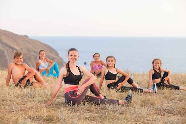 Instructeur traint yogakinderen in de bergen aan de oceaan.