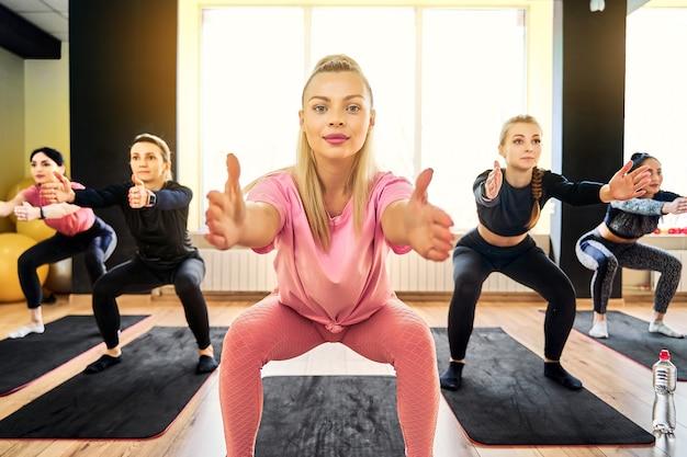 Instructeur vrouw squat oefening bij groepsfitness training