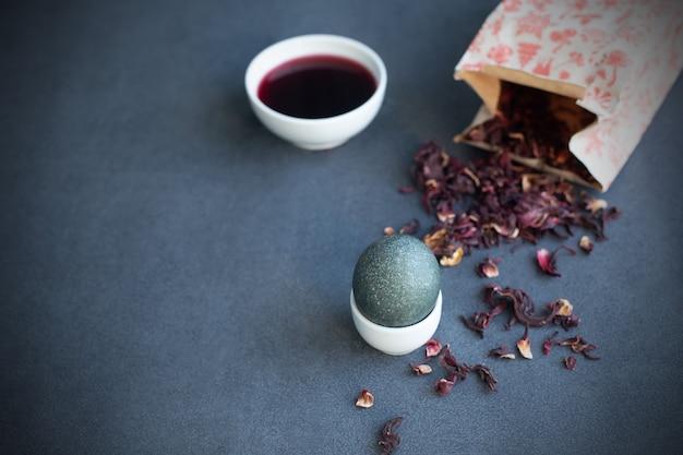 Instructies voor het kleuren van paaseieren met natuurlijke kleurstof. grijze kleur van carcade-thee. kopieer ruimte. grijze achtergrond