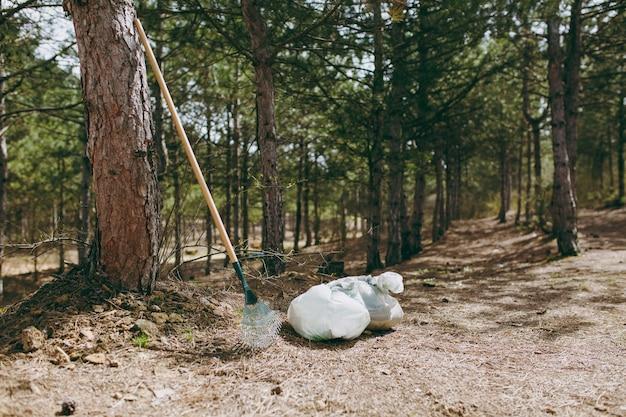Instrumenten hark voor afvalinzameling, vuilniszakken tussen struiken en bomen in park of bos. rommel opruimen. probleem van milieuvervuiling
