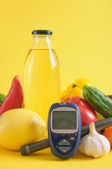 Insulinespuitpen, digitale glucometer en groenten op gele achtergrond. pitaniye pri diabete