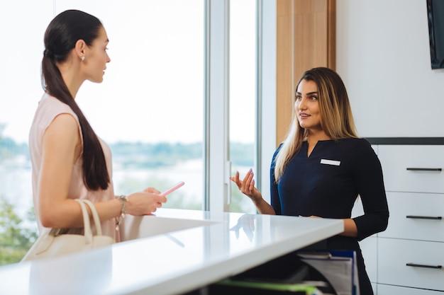 Intelligente aardige vrouw die met de klant praat tijdens het werken bij de receptie