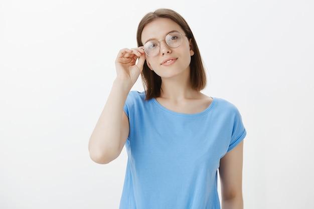 Intelligente jonge vrouw die in glazen hoopvol kijkt en glimlacht