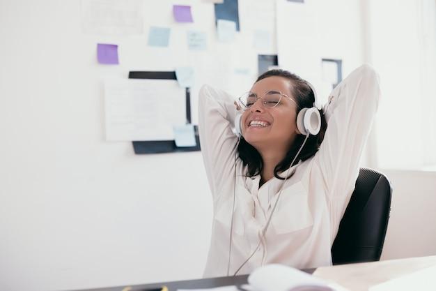 Intelligente jonge vrouw met armen op het hoofd ontspant het luisteren naar muziek