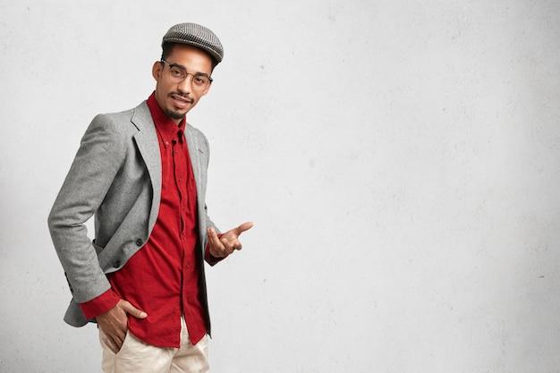 Intelligente jongeman draagt pet, formeel rood shirt met jasje en ronde bril, heeft zelfverzekerde uitdrukking