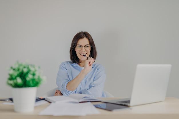 Intelligente prachtige vrouw gekleed terloops werkt thuis, zit achter geopende laptop