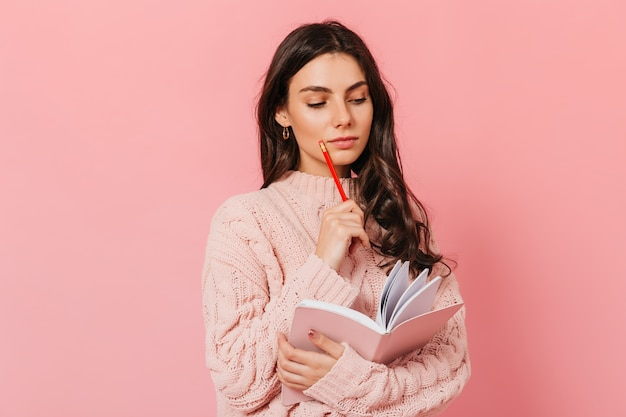 Intelligente vrouw in roze trui denkt aan het vervolg van haar boek. brunette kijkt in haar dagboek op roze achtergrond.