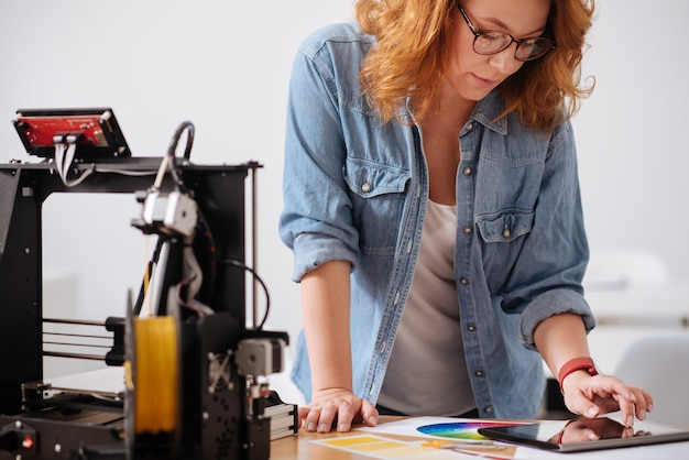 Intelligente vrouwelijke 3d-ontwerper die zich in de buurt van de tafel bevindt en ernaar leunt tijdens het werken op een tablet