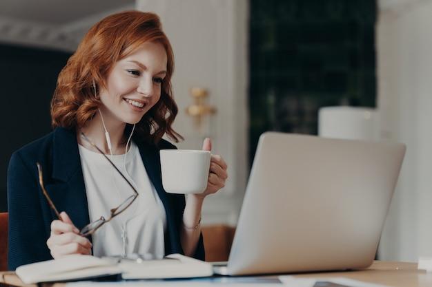 Intelligente vrouwelijke student heeft online cursus, geconcentreerd in scherm van laptopcomputer