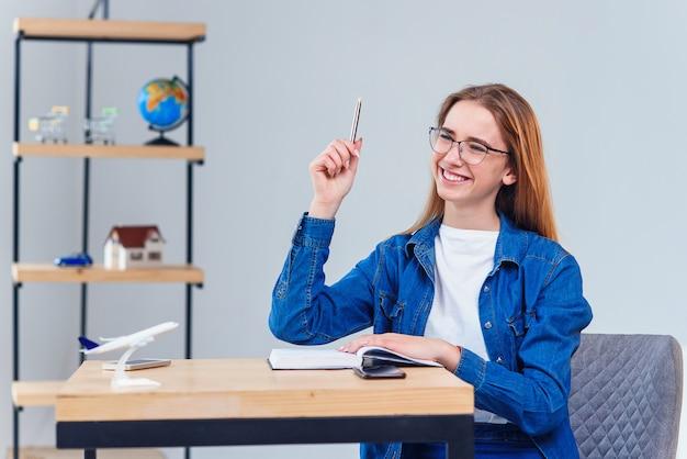 Intelligente vrouwelijke student krijgt onverwacht geweldig idee terwijl hij thuis studeert, student komt tot materieel begrip of bereikt het punt dat studeert in een coworking-kantoor.