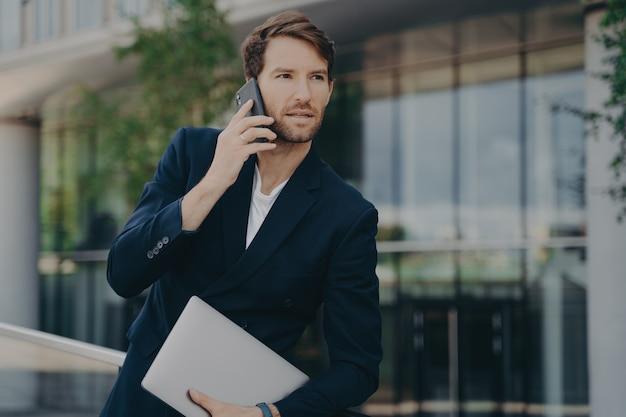 Intelligente zakenman spreekt aan de telefoon tijdens wandeling naar kantoor
