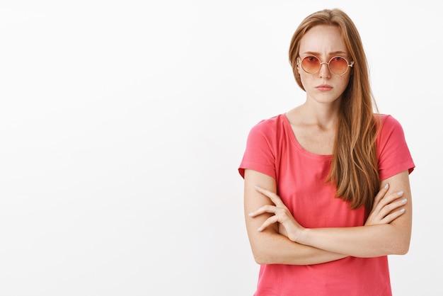 Intens ernstig ogende ontevreden roodharige meisje met sproeten in zonnebril en roze t-shrit fronsend hand in hand gekruist op borst, boos en ontevreden voelen