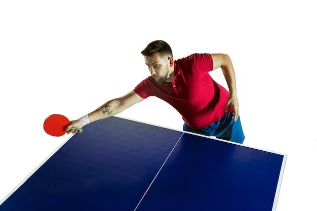 Intens. jonge man speelt tafeltennis op witte muur. model speelt pingpong. concept van vrijetijdsbesteding, sport, menselijke emoties in gameplay, gezonde levensstijl, beweging, actie, beweging.
