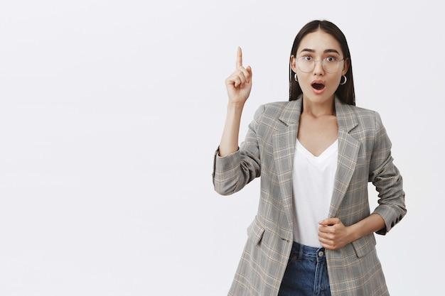 Intens opgewonden volwassen vrouwtje in bril en jasje, wijsvinger opheffend in eureka-gebaar, snakkend, interessante gedachte zeggend