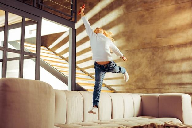Interactie thuis. opgetogen blonde jongen die zijn evenwicht bewaart terwijl hij op de bank springt
