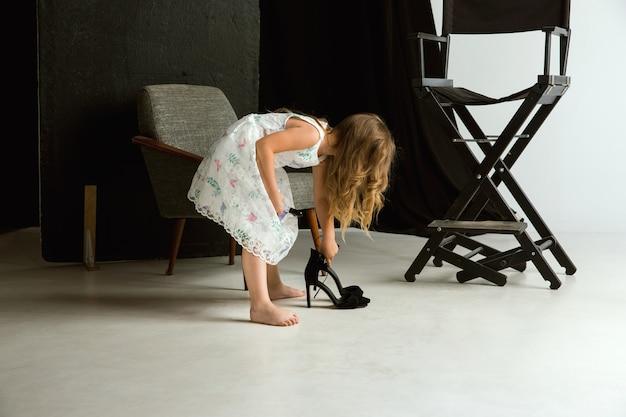Interactie van kinderen met volwassen wereld. leuk meisje dat de overmaatse schoenen van mama draagt en zich kleedt omdat ze ouder is zoals zij is. klein vrouwelijk model dat thuis kleding probeert. jeugd, stijl, droomconcept.