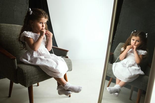 Interactie van kinderen met volwassen wereld. schattig meisje probeert een lichte make-up te doen omdat ze ouder is. klein vrouwelijk model dat mama's cosmetica thuis probeert. jeugd, stijl, mode, droomconcept.