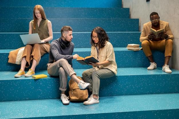 Intercultureel paar studenten die boek bespreken terwijl ze op de trap zitten