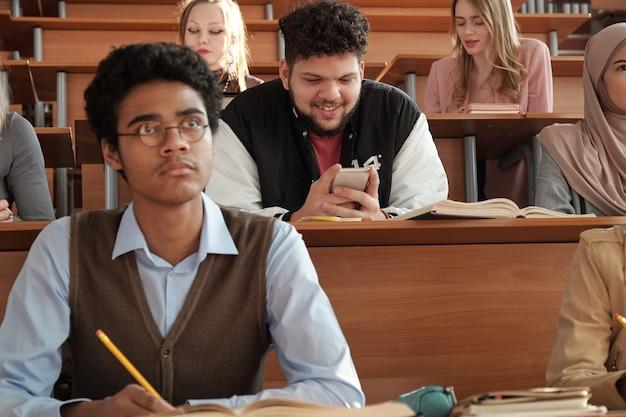 Interculturele studenten zitten in rijen bij bureaus tijdens college