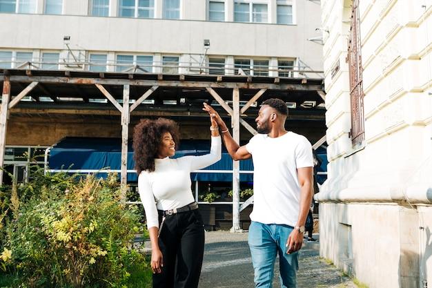 Interculturele vrienden high five op straat
