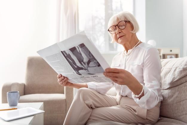 Interessant artikel. mooie senior dame zittend op de bank in de woonkamer en een krant lezen, aandacht schenken aan