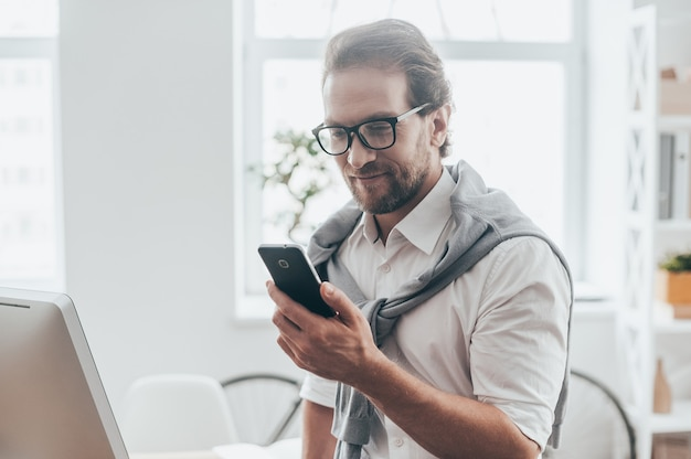 Interessant bericht. knappe jongeman die lacht en naar de telefoon kijkt terwijl hij op het bureau zit op zijn werkplek in een creatief kantoor