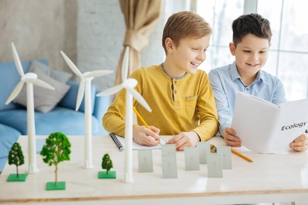 Interessant boek. aangename pre-tienerjongens die het boek over ecologie lezen voor hun schoolproject terwijl een van de jongens aantekeningen maakt in zijn notitieboekje