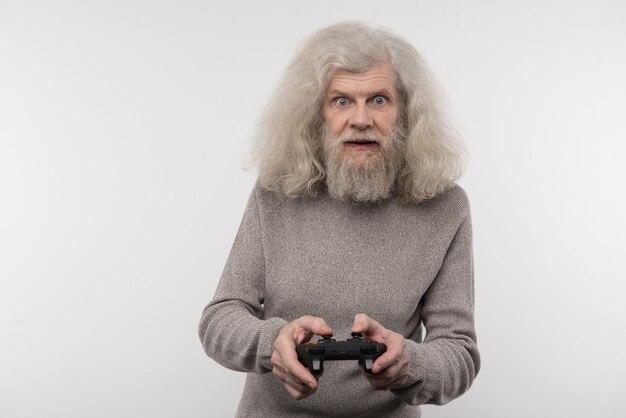 Interessant entertainment. opgewonden oudere man met een gameconsole terwijl hij geniet van het spel